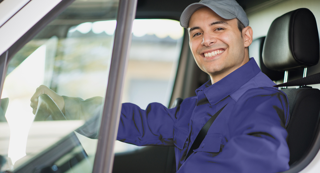 A man smiles while sitting in a van.